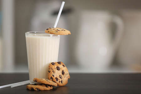 Glass of milk with cookies on table