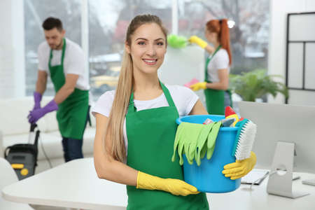 Young female worker holding cleaning supplies at office Stock fotó