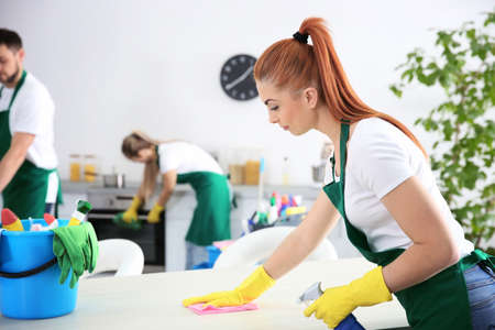 Young female worker of cleaning service working in kitchen 写真素材
