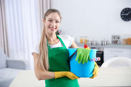 Young female worker with cleaning supplies in kitchen