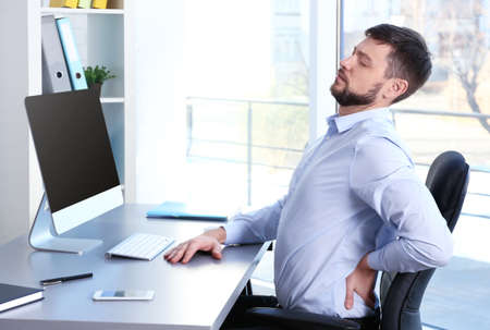 姿勢の概念。オフィスでコンピュータを操作しながら腰痛に苦しむ男性