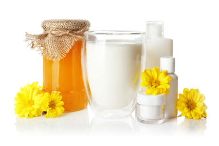 Honey, milk and cosmetics on white background