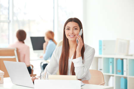 Beautiful young woman talking by mobile phone while working in office