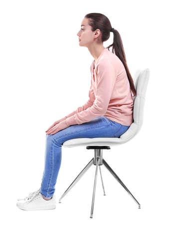 Haltungskonzept. Junge Frau, die auf Stuhl gegen weißen Hintergrund sitzt