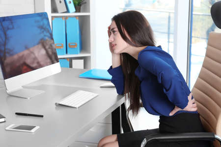 Posture concept. Young woman suffering from back pain while working with computer at office