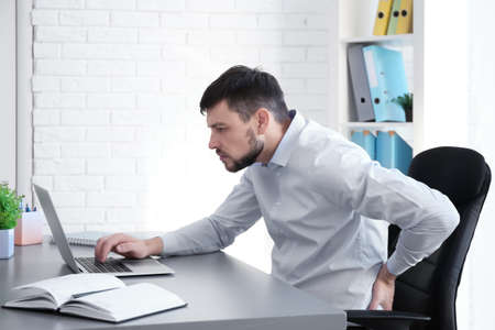 Posture concept. Man suffering from back pain while working with laptop at office Stockfoto - 104566188