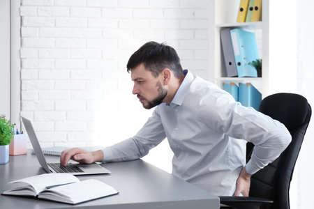ポスチャコンセプト。オフィスでラップトップで作業中に背中の痛みに苦しむ男性