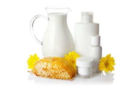 Honeycomb, milk and cosmetics on white background
