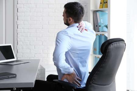 concept de posture . homme souffrant de maux de dos tout en travaillant avec ordinateur portable au bureau