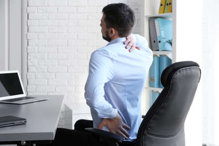 Posture concept. Man suffering from back pain while working with laptop at office