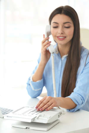 Young woman dialing telephone number in office Stock Photo