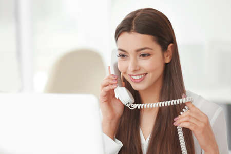 Beautiful young woman talking by telephone while working with computer in office