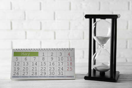 Hourglass with calender on brick wall background Stock Photo