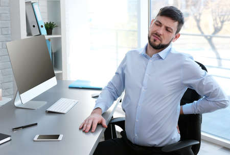 Posture concept. Man suffering from back pain while working with computer at office Stock Photo