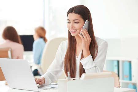 Schöne junge Frau, die durch Handy während der Arbeit im Büro spricht