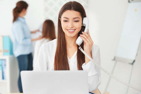 Beautiful young woman talking by telephone while working in office Stock Photo