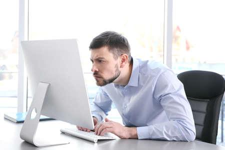 Concepto de postura. Hombre que trabaja con la computadora en la oficina Foto de archivo