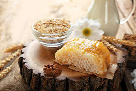 Composition of honeycomb, oatmeal and milk on wooden background