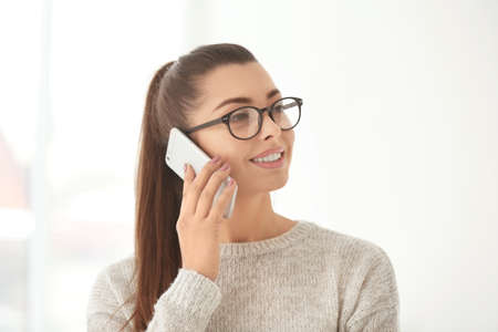Beautiful young woman with glasses talking by mobile phone indoors