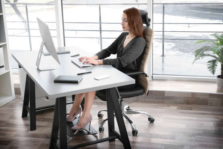 Concepto de postura. Mujer joven que trabaja con la computadora en la oficina