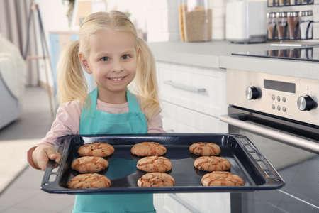 Kleines Mädchen, das Kekse auf Tablett hält Standard-Bild