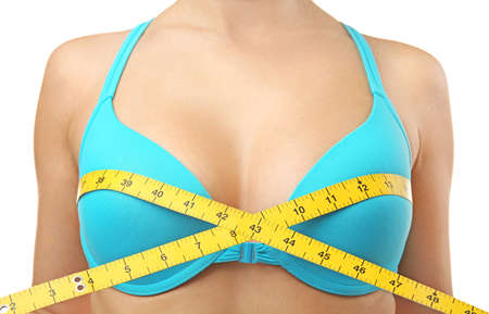 Young woman in blue bra with measuring tape on white background