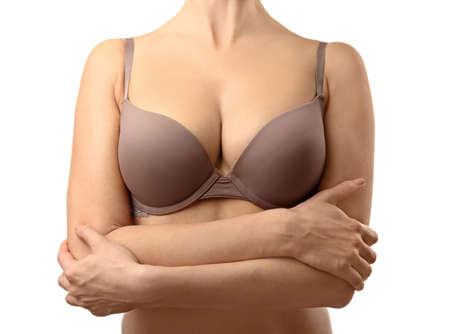 Mujer joven en sujetador beige sobre fondo blanco.