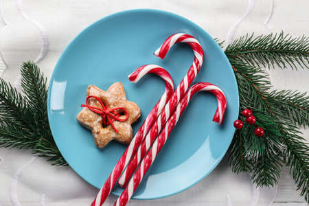 Plate with candy canes and Christmas decorations on napkin Stock Photo