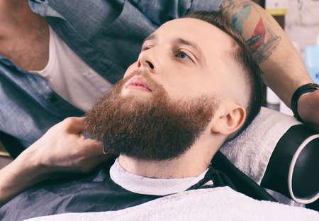 Hairdresser shaving client in barbershop Foto de archivo