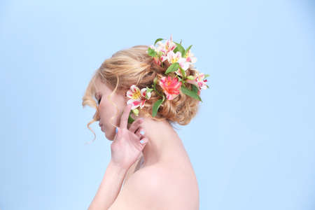 Beautiful young woman with flowers in hair on light background