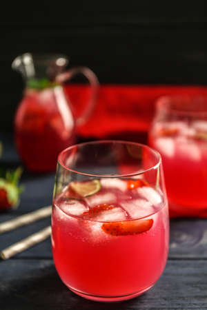 Refreshing cocktails with strawberry on wooden table