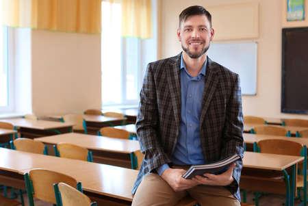 Portrait of happy teacher in classroom