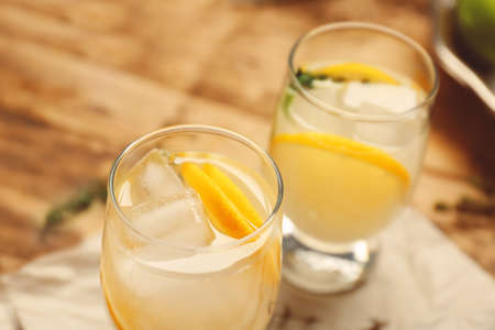 Refreshing cocktails with lemon on wooden table