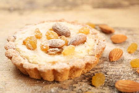 Delicious crispy tart with sugar powder, almond and raisins on table, closeup