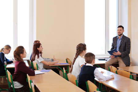 Pupils listening teacher in classroom