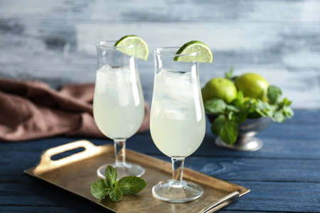 Tray with refreshing cocktails and lime on wooden table