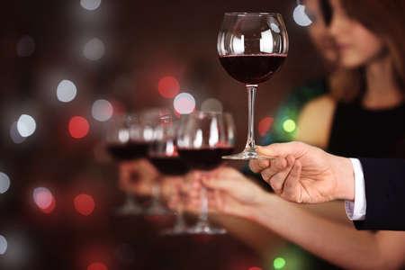 Male hand taking wine glass against defocused lights