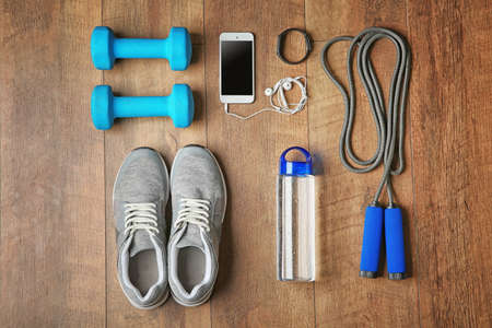 Sport sneakers and equipment on wooden background