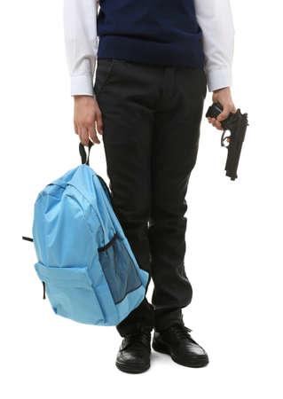 Schoolboy holding backpack and gun on white background Stock Photo