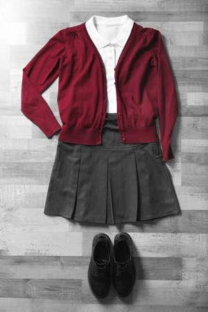Clothes of schoolgirl on wooden floor, flat lay 写真素材