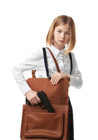 Schoolgirl hiding gun in bag on white background Stock Photo