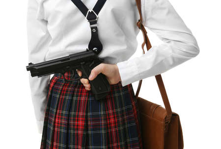 Schoolgirl hiding gun behind her back on white background