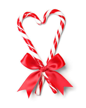 Heart shape made with candy canes on white background