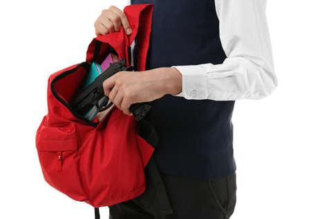 Schoolboy hiding gun in backpack on white background