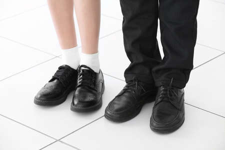 Piernas de niña y niño sobre fondo de piso de baldosas