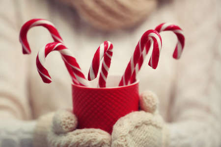 Woman holding cup with candy canes, closeup Stock Photo