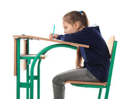 Incorrect posture concept. Little girl sitting at school desk on white background Reklamní fotografie