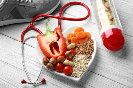 Healthy food and stethoscope on wooden background Stock Photo