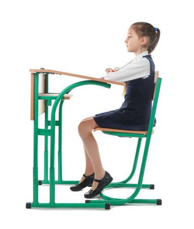 Incorrect posture concept. Little girl sitting at school desk on white background 版權商用圖片