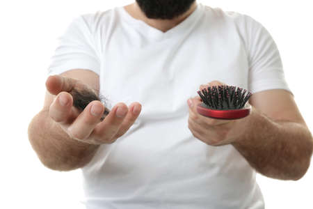 Adult man with hair brush on white background, closeup. Hair loss concept Stock Photo